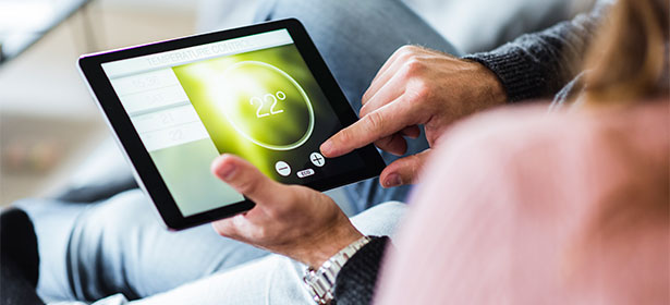 Hands using a smart heating app on a tablet