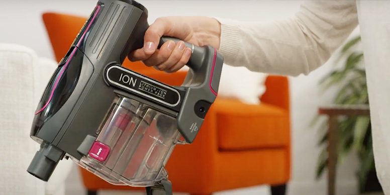 A closeup up the dust container, battery and handle of a Shark cordless vacuum