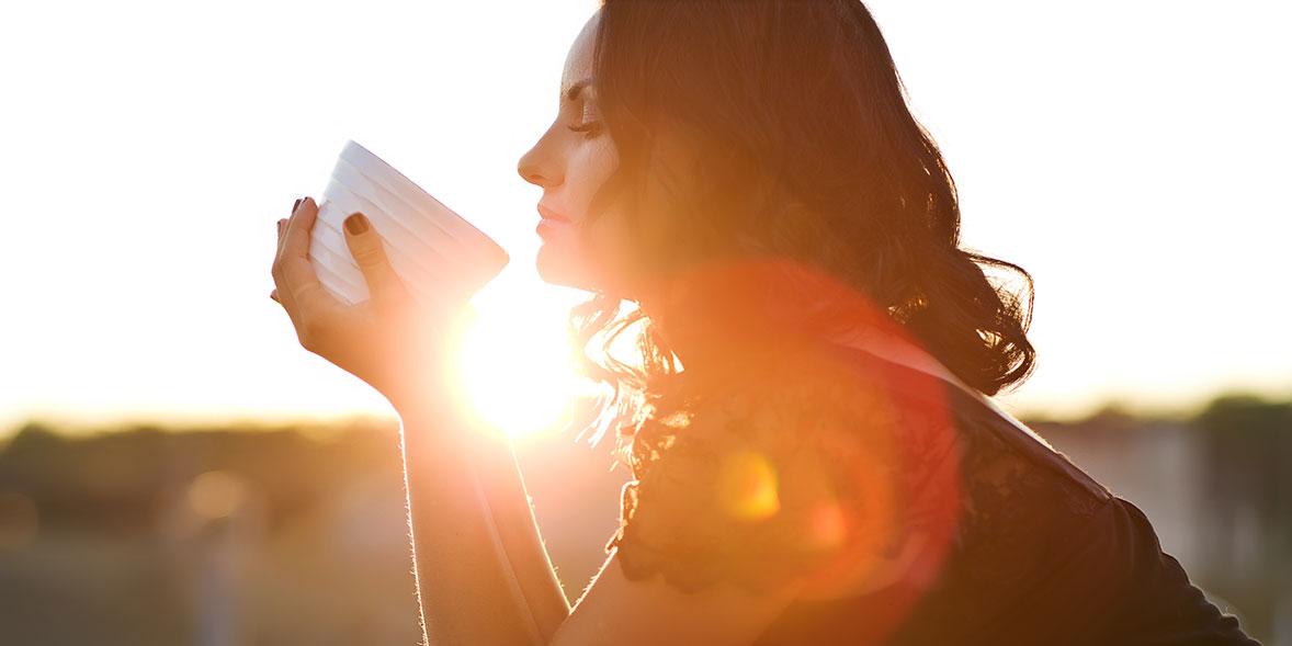 Lady enjoying coffee at sunset