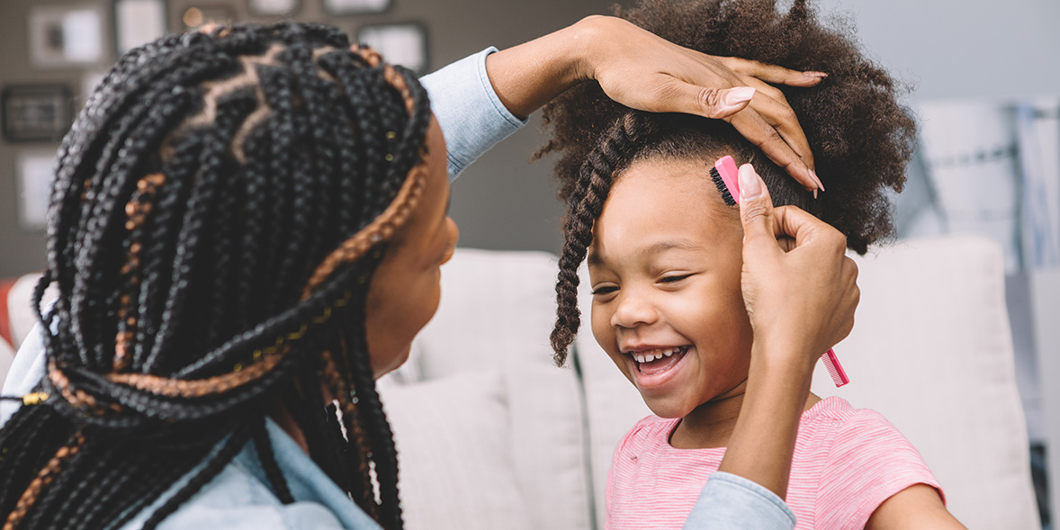 Mother combing child with afro hair