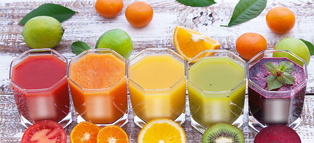 Several glasses of different juice lined up on a kitchen counter.