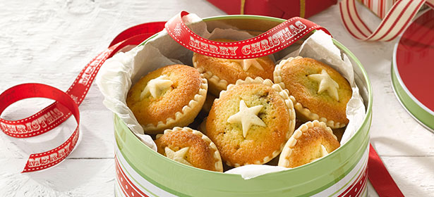 mince pies in a round green tin with a merry christmas ribbon