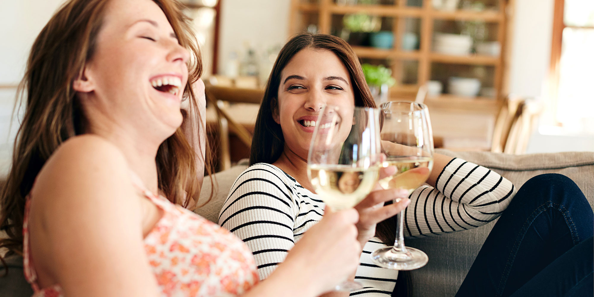 Two people laughing and holding glasses of white wine