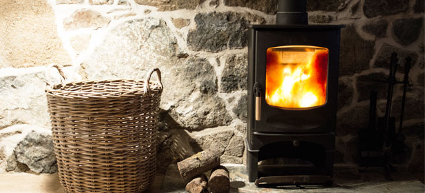 Wood burning stove with a basket of wood logs nearby 481367