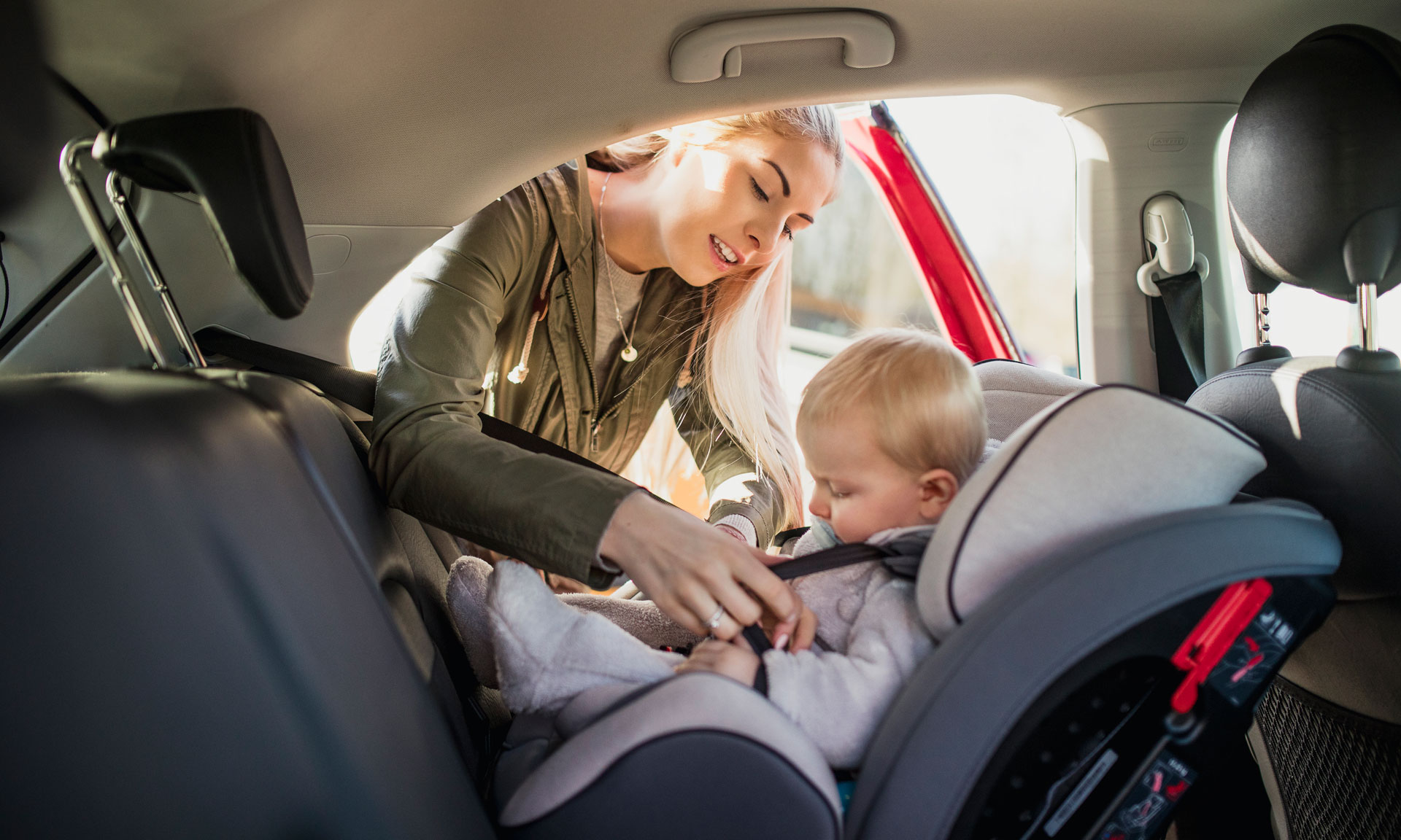 Mum strapping child in car seat