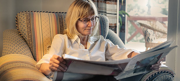 Woman wearing glasses and reading paper 448541