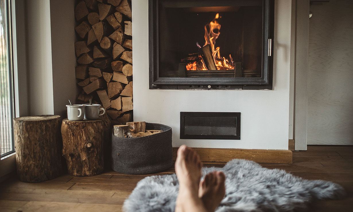 person putting feet up in front of a fire