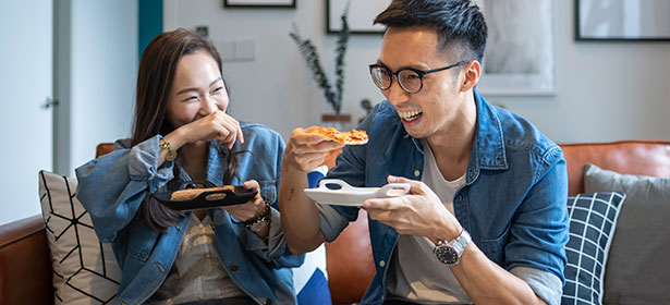 Two people smiling and eating pizza