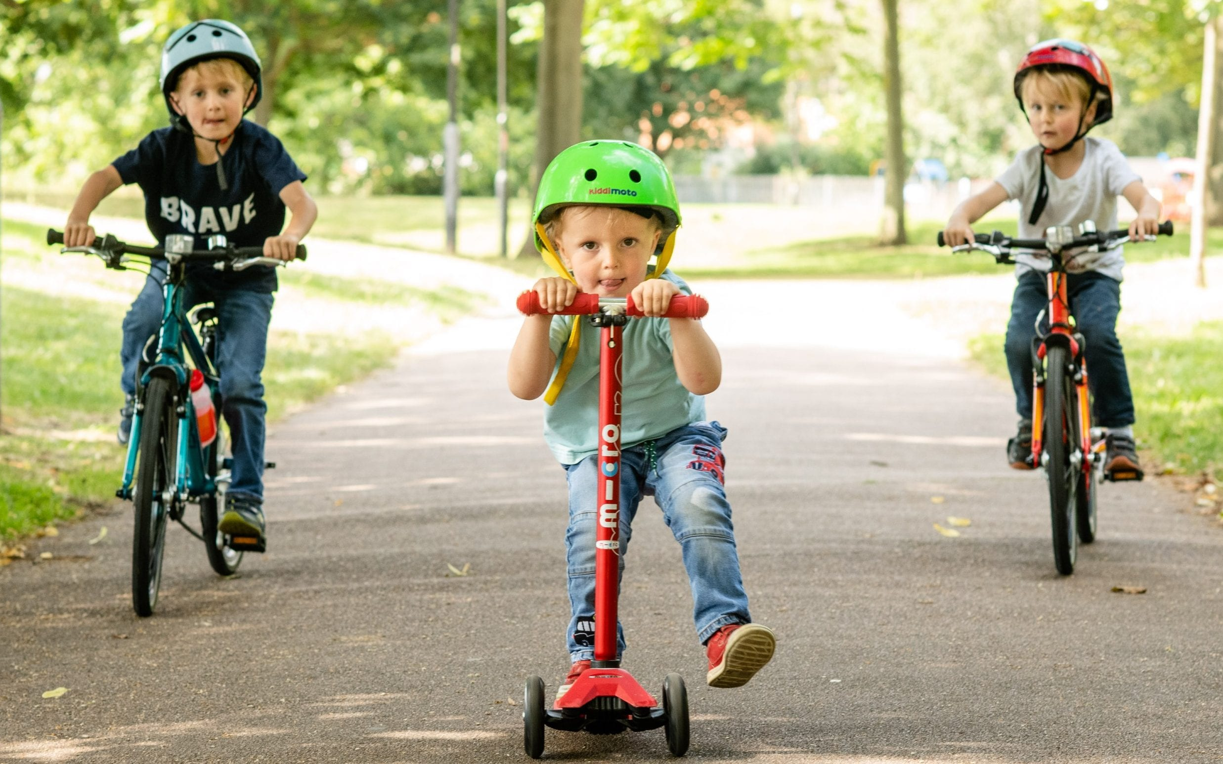 Children riding bikes and scooters in a park