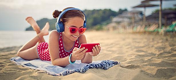 Girl using wireless headphones on beach