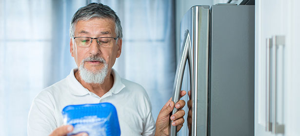 Man looking at food from the fridge.