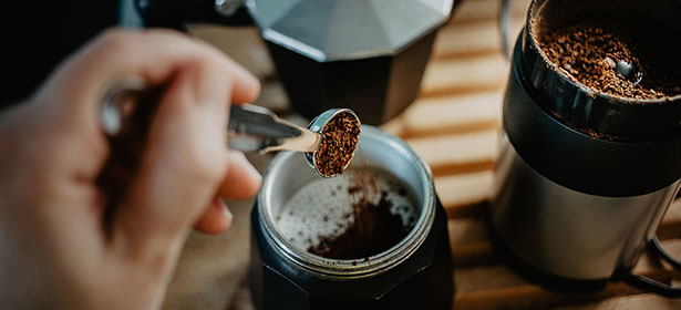 Scooping coffee grinds out of a coffee grinder