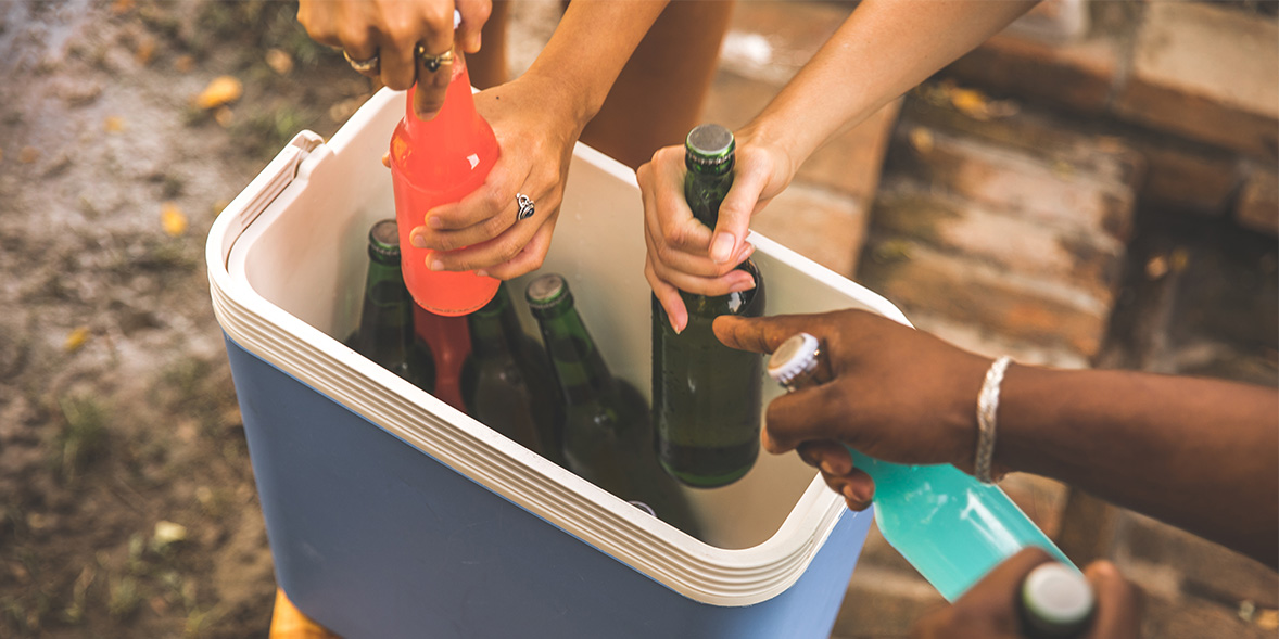 People getting drinks out of a cooler.