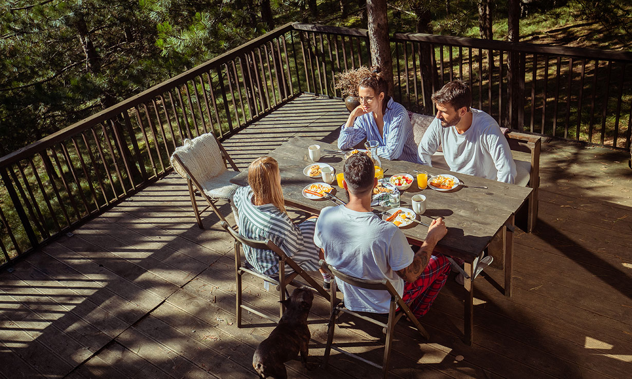 group of people at table in forest cottage holiday
