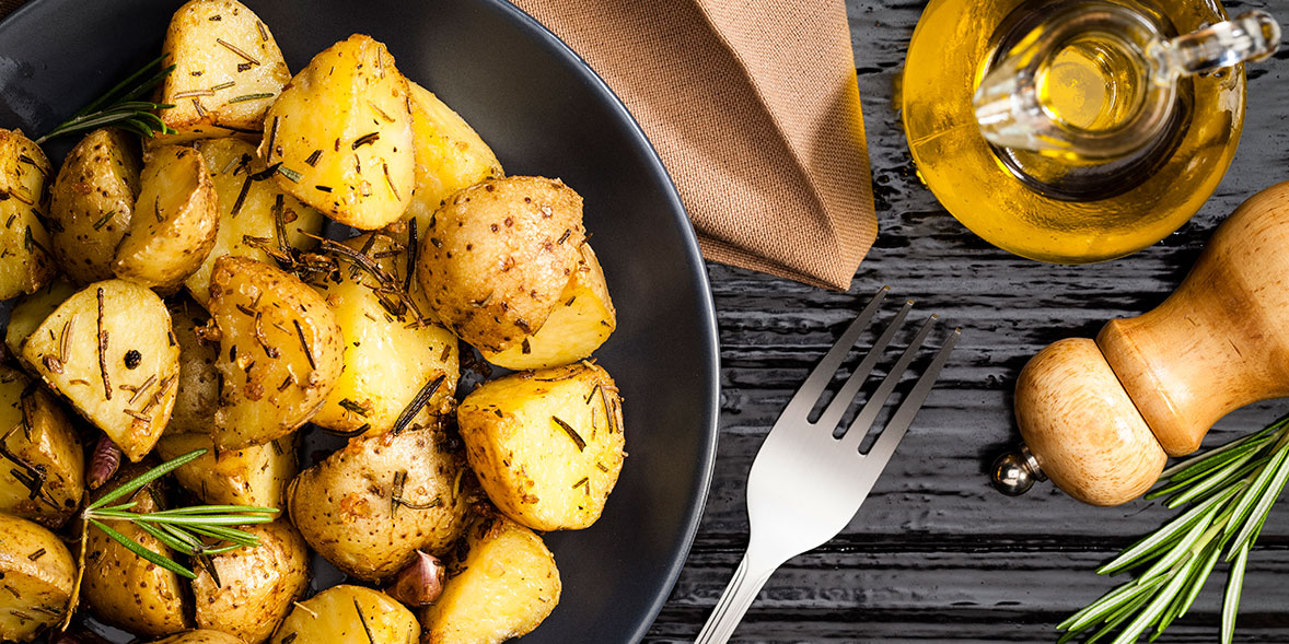 Dish of roast potatoes with sprig of rosemary