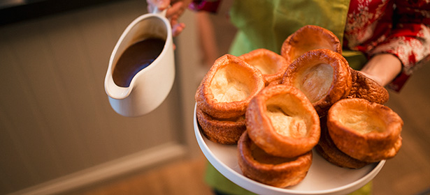 Yorkshire puddings on plate with jug of gravy