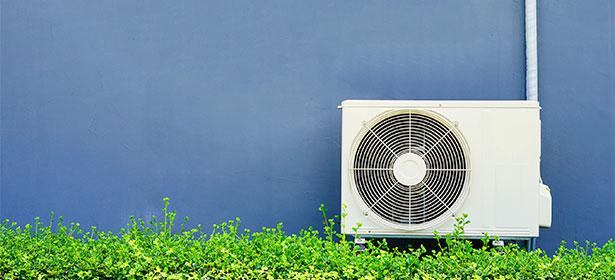 Air source heat pump next to a blue wall