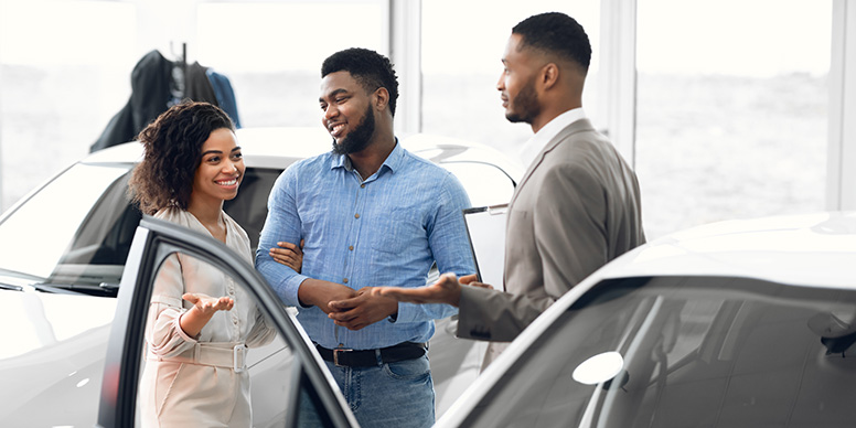Couple and car dealer in showroom