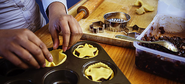 pressing pastry circle into muffin tin to make mince pies