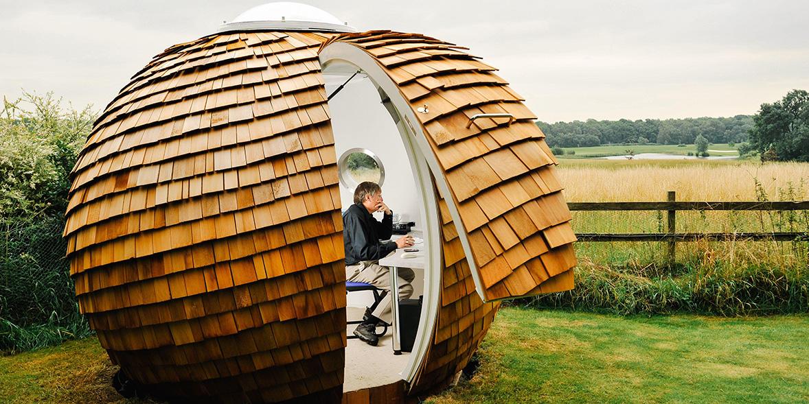 Man sitting in a circular tiled garden office next to a field