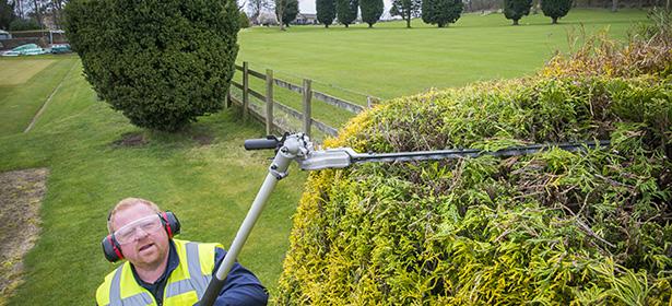 man using a long-reach hedge trimmer