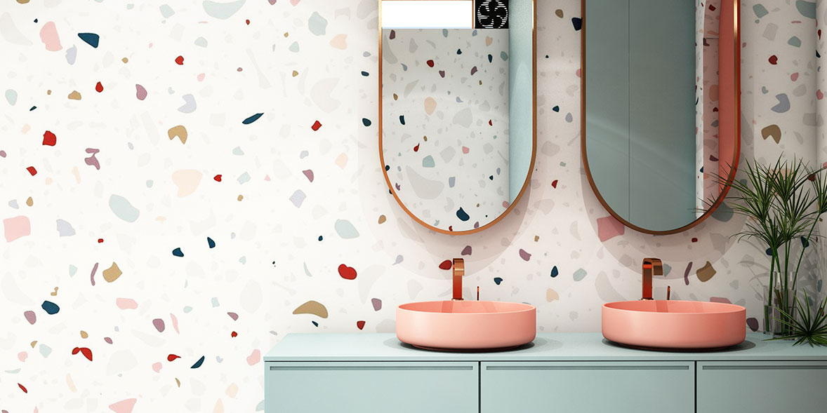 Bathroom wallpaper with a white background and different shapes of colour on a bathroom wall with two pink sinks and a pale green bathroom vanity unit