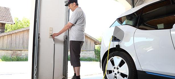 Man charging car in garage
