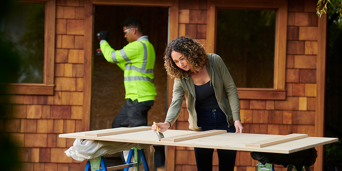 Woman painting a wooden garden room