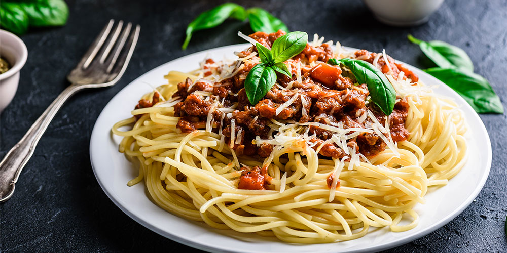 Spaghetti bolognese topped with grated cheese and fresh basil