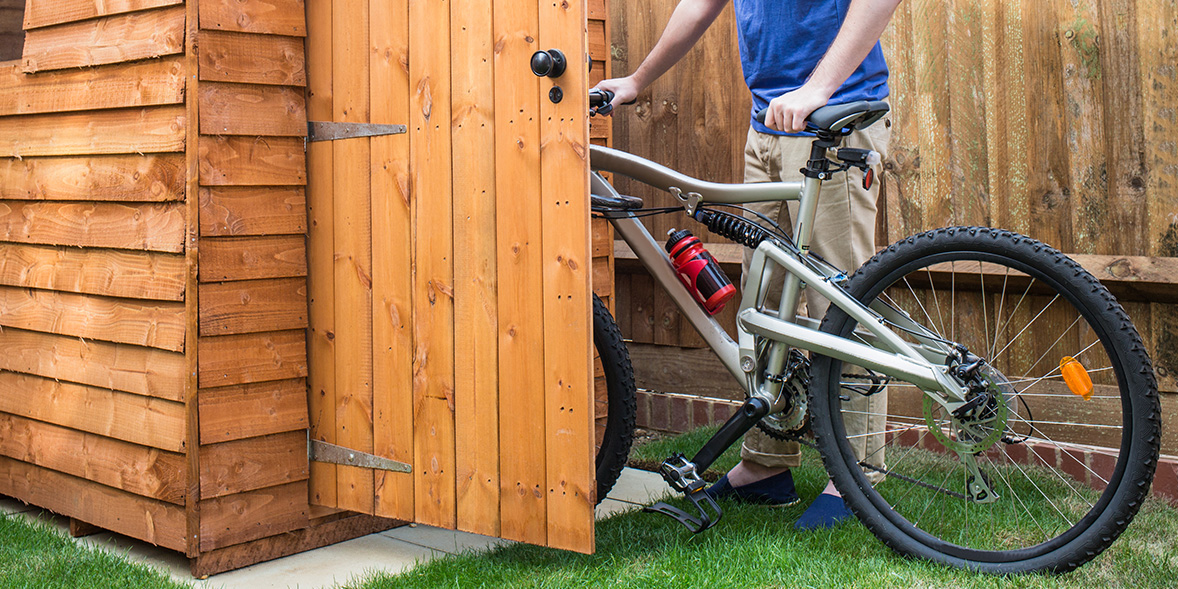 cyclist putting bike in shed