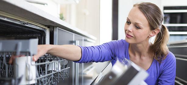 Woman loads integrated dishwasher