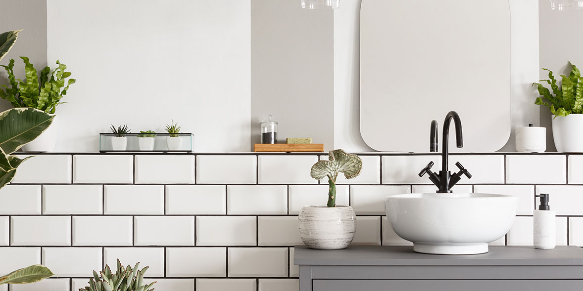 White bathroom tiles around a grey vanity unit with a white sink and black mixer tap