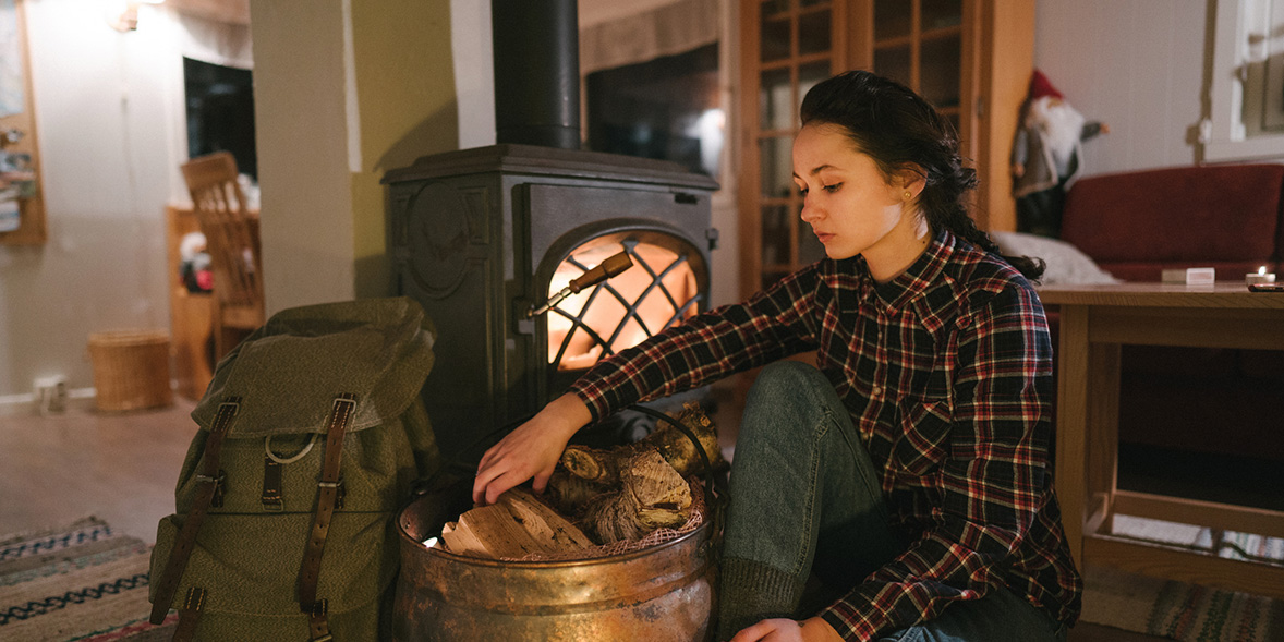 Woman sitting by a stove with a bucket of dry wood
