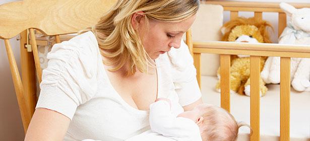 Mum sitting in nursery breast feeding