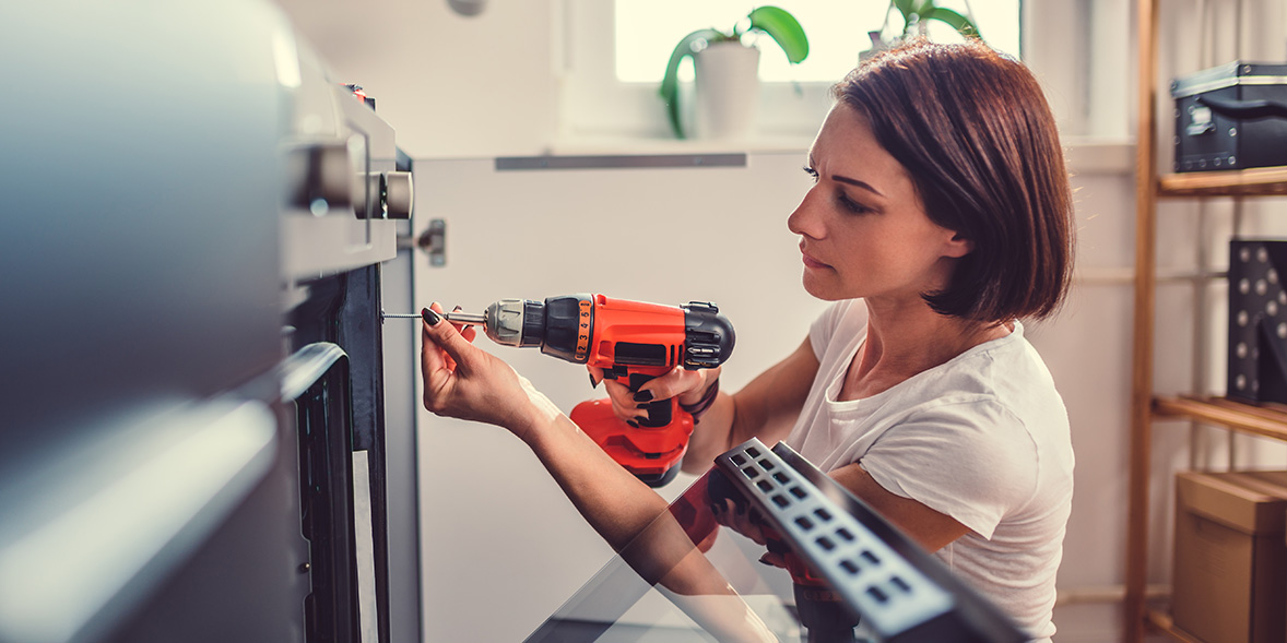 Woman drilling with a cordless drill.