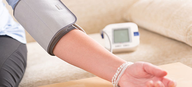 Woman using arm blood pressure monitor