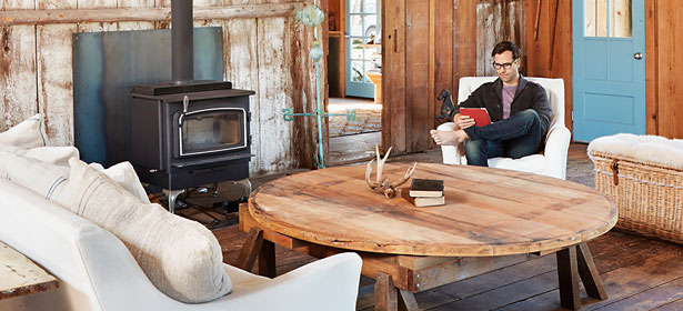 Man reading by wood burning stove