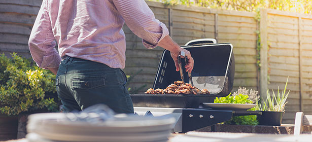 Man using a barbecue to cook meat