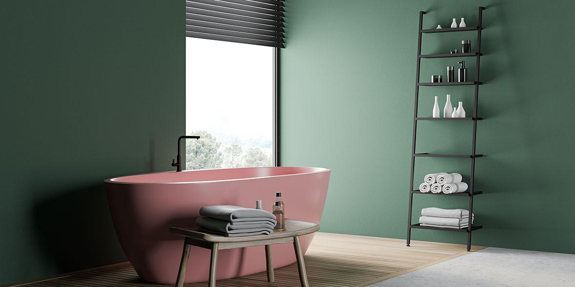 Deep green bathroom with a pastel pink bath, black tap and dark wood shelf ladder