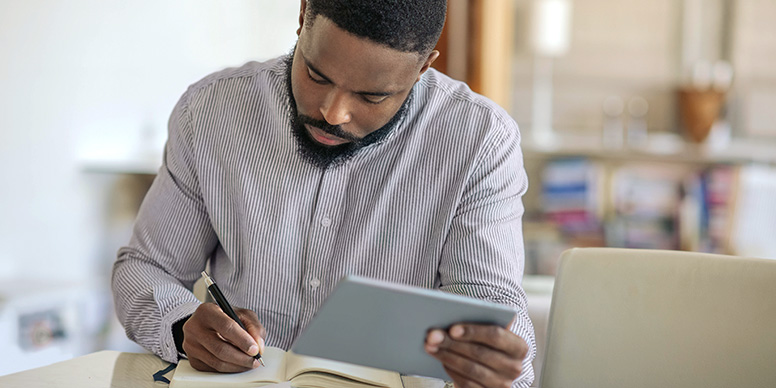Man using a tablet and taking notes