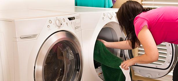 Woman loading tumble dryer next to washing machine