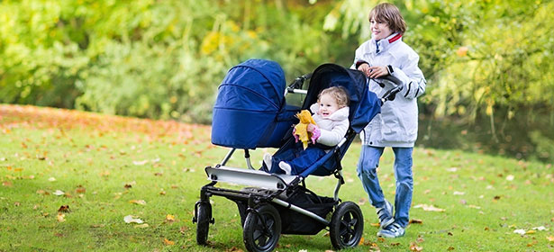 Child pushing baby in double pushchair