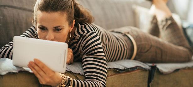 Woman using tablet on sofa