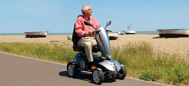 Man on mobility scooter by the sea 429431