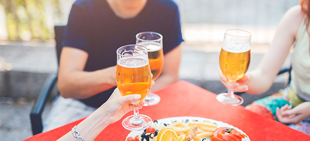 Three people toasting glasses of beer at a table