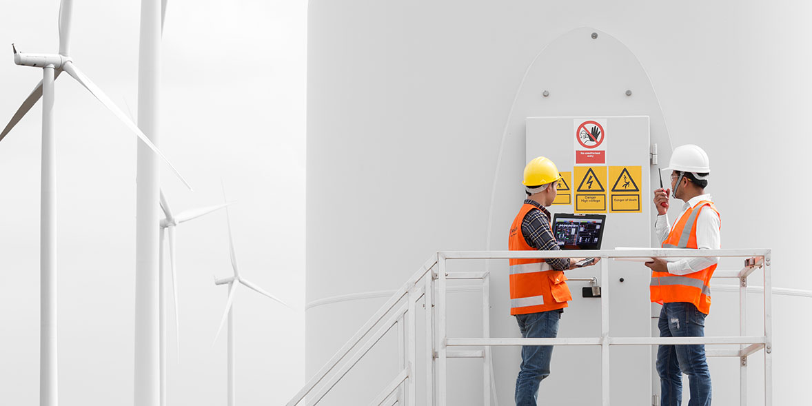 Two employees in high-vis working at a wind turbine