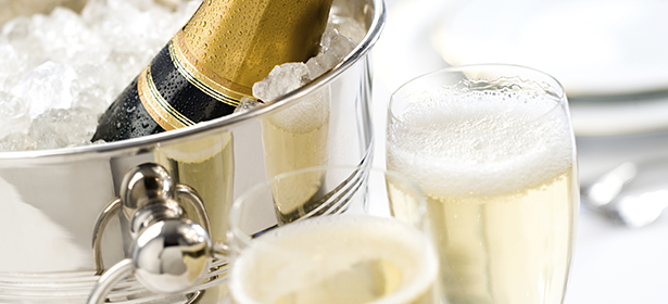 Bottle of champagne in a bucket of ice next to two glasses of champagne