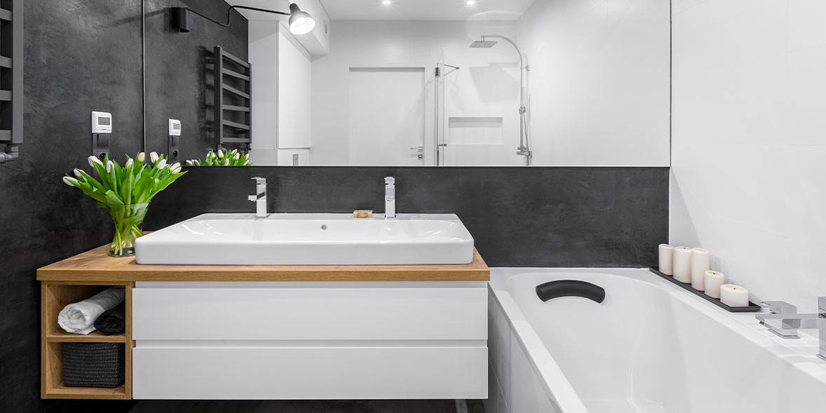 Double bathroom sink in a block bathroom on a white and wood vanity unit
