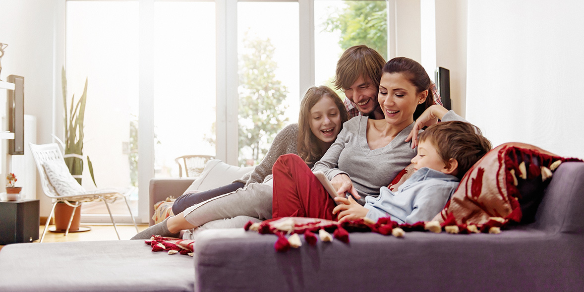 Family sitting on a sofa in a warm home