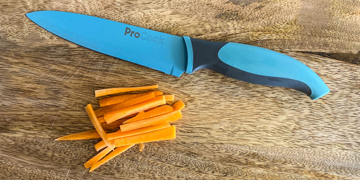 A pile of carrot juliennes next to a ProCook Chefs Knife